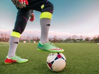 Fussballspieler mit Fuß auf dem Ball