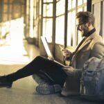 Mann mit Smartphone und Laptop-Rucksack